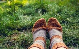 Fot i varma woolen sockor stucken sockaull Fot i sockor på bakgrunden av grönt gräs Höstbegrepp, lopp royaltyfri fotografi