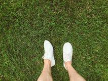 Fot i vita gymnastikskor på gräset arkivfoto