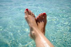 Fot med röd pedikyr av flickan på bakgrunden av havet Flicka på semesterorten Kvinnlig fot på havsbakgrund Royaltyfria Foton