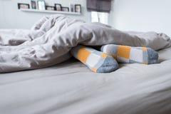 Fot med sockor, fot på sängen under filten Arkivfoton