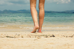 Fot och ben av den unga kvinnan som går på stranden Arkivbilder