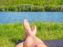 Fot på sjön/floden, äng/gräs Arkivbild