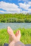 Fot på sjön/floden, äng/gräs Arkivfoto