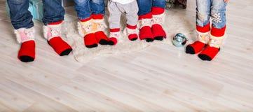 Fot som bär julsockor på det wood golvet lycklig utgångspunkt för familj Xmas semestrar begrepp arkivbilder