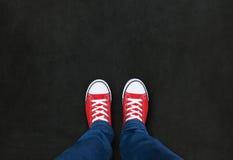 Fot som bär röda skor på svart bakgrund Royaltyfri Bild