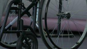Fot som vilar på rullstolar moment, man som framdriver rullstolen för att flytta sig framåtriktat arkivfilmer