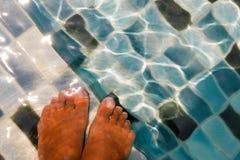 Fot under det genomskinliga vattnet Arkivfoton