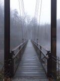 Fot- upphängningbro över floden arkivfoton