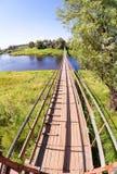 Fot- upphängningbro av stål och trä över floden Arkivbilder