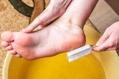 Fotbad Omsorg för torr hud på fot och häl Använda pedikyrpolermedelhjälpmedel och en borste royaltyfria bilder
