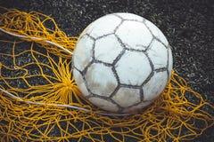 Fotboll- eller fotbollboll på gräset bredvid det netto för bollar, närbild arkivbild