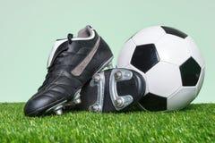 Fotboll eller fotbollkängor och boll på gräs arkivfoton