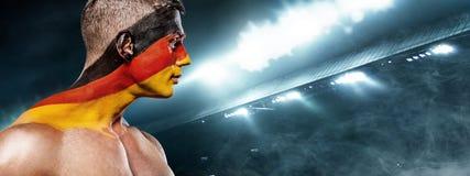Fotboll eller fotbollsfan på stadion med bodyart på framsidan - flagga av Tyskland, Deutschland Arkivfoton