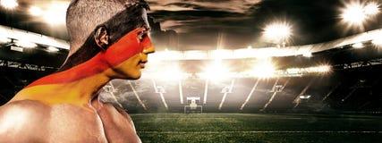 Fotboll eller fotbollsfan på stadion med bodyart på framsidan - flagga av Tyskland, Deutschland Fotografering för Bildbyråer