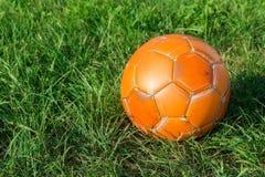 fotboll för orange för bollgräsgreen Begreppet av gatafotboll royaltyfri bild