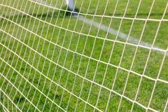 Fotboll förtjänar på mål bak tillbaka sikt på fält Royaltyfri Foto