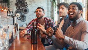 Fotboll i bar Vänner som håller ögonen på matchen i sportstång arkivfoton