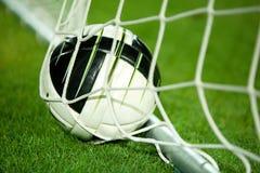 Fotboll klumpa ihop sig i netto fotografering för bildbyråer
