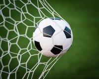 Fotboll klumpa ihop sig i mål netto Arkivbild