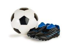 Fotboll klumpa ihop sig, och fotboll skor Arkivfoto