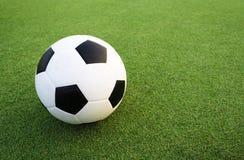 Fotboll klumpa ihop sig på gräsplan sätter in Arkivfoton