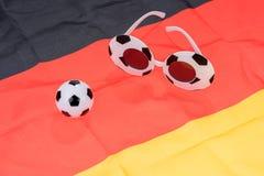 Fotboll- och abstrakt begreppexponeringsglas på den tyska flaggan Arkivbild