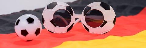 Fotboll- och abstrakt begreppexponeringsglas på den tyska flaggan Arkivfoton