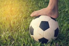Fotboll och fot på det gröna gräset Arkivbild