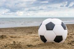 Fotboll på den öde stranden royaltyfria bilder