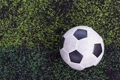 Fotboll på konstgjort grönt gräs Arkivfoto
