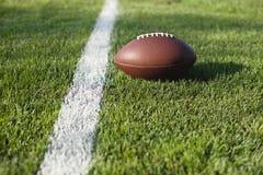 Fotboll på mållinjen på gräsfält Arkivbild