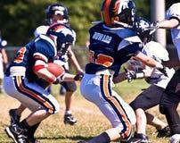 fotboll som gör landningsögonblickungdommen Arkivbild