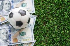 Fotbollaffärsidé: En fooball på dollarräkningar och gräsplan royaltyfri foto