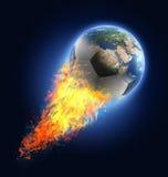 Fotbollboll i flammor som omformar in i jord Arkivfoton