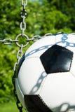 Fotbollboll i målet med kedjor och slut för naturlig bakgrund upp royaltyfria bilder