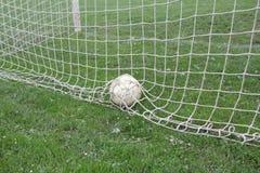 Fotbollboll i netto Arkivfoton
