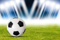 Fotbollboll i stadion mot fläckljus Arkivfoto