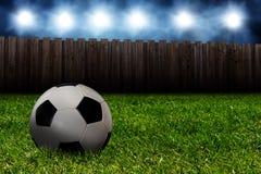 Fotbollboll i trädgården på natten Arkivfoto