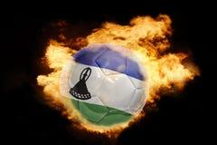 Fotbollboll med flaggan av Lesotho på brand Royaltyfria Foton