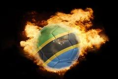 Fotbollboll med flaggan av Tanzania på brand Fotografering för Bildbyråer