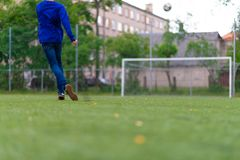Fotbollboll med hans fot på fotbollfältet arkivbild