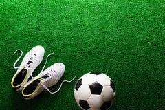 Fotbollboll och dubbar mot grön konstgjord torva, studiosho Arkivfoton