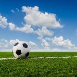 Fotbollboll på det gröna gräset av fotbollfältet Arkivfoton