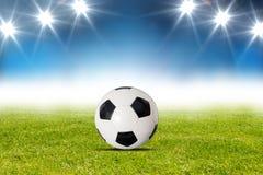Fotbollboll på gräset med fläckljus Royaltyfri Foto