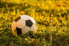Fotbollboll som ligger på det gröna gräset royaltyfri foto