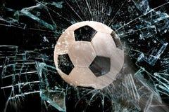 Fotbollboll till och med exponeringsglas Arkivfoto