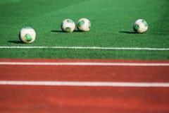 Fotbollbollar på fältet Royaltyfria Bilder
