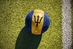 Fotbollbollen med nationsflaggan av Barbados ligger på fältet Royaltyfri Bild