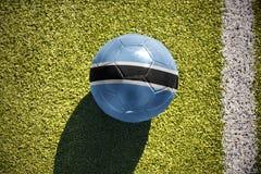 Fotbollbollen med nationsflaggan av Botswana ligger på fältet Royaltyfri Foto