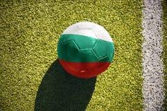 Fotbollbollen med nationsflaggan av Bulgarien ligger på fältet Fotografering för Bildbyråer
